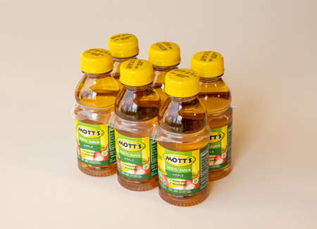 BEMIDJI, MN - 17 NOV 2020: Plastic bottles of Motts apple juice in 6 pack state on the label that the product contains 100 percent juice. Редакционное