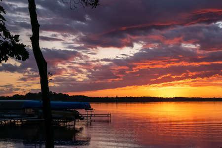 Sunset reflecting in the water of a beautiful lake and trees, dock, boat lifts in the foreground in Bemidj, Minnesota.