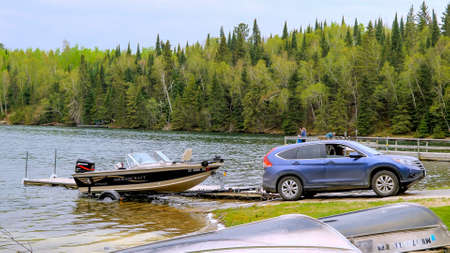 CLEARWATER CO, MN - 23 MAY 2020: Fishing boat with outboard motor on a trailer is pulled out of the water by an automobile at a Minnesota lake.