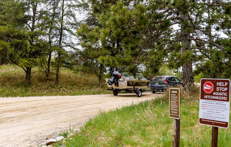 CLEARWATER CO, MN - 23 MAY 2020: Automobile car pulls fishing boat and trailer on a gravel road near a Minnesota lake and past signs about invasive species.