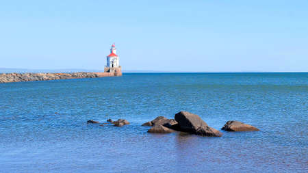 Lighthouse with red roof at the end of a pier on Lake Superior, and large boulders surrounded by ripples of blue water being blown away from the camera by the wind. 스톡 콘텐츠