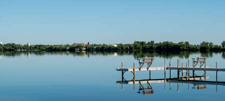 An inviting boat dock is reflected in the glassy water of Lake Irving, the first lake on the Mississippi river, with Bemidji, Minnesota, the 2018 Best Town in Minnesota, seen across the lake.