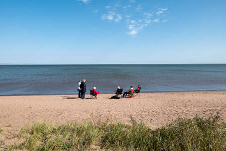Sand beach and grass covered sand dunes on the shore of the Great Lake, Superior, at Wisonsin Point on a sunny day, with several senior people enjoying the waterfront.