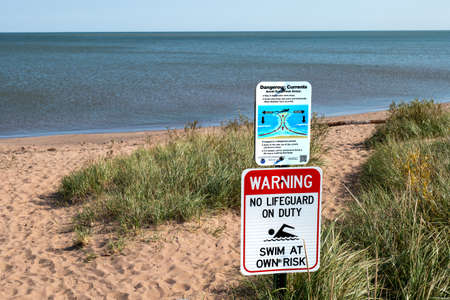 SUPERIOR, WI - 5 OCT 2020: Warning Signs at public swimming beach area at lake shore on a sunny day. Lake Superior at Wisconsin Point.