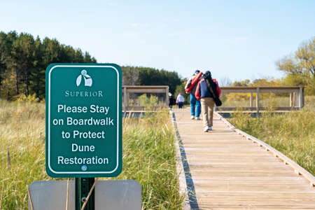 SUPERIOR, WI - 5 OCT 2020: Green sign next to a boardwalk over dune at Wisconsin Point, with people walking on the wooden walkway. 에디토리얼