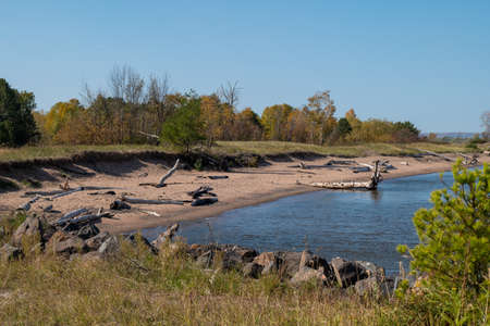 Lake Superior shore at Wisconsin Point, with blue water and sky, autumn trees, sand beach, rocks and driftwowod on a sunny day.