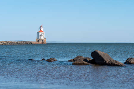 Lighthouse with red roof at the end of a pier on Lake Superior, and large boulders surrounded by ripples of blue water.