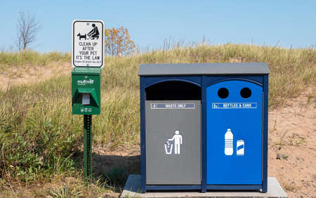 SUPERIOR, WI - 5 OCT 2020: Waste and Recycle containers and Dog feces bags and reminder sign at public park on Wisconsin Point. 에디토리얼