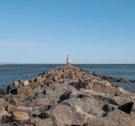 Lighthouse with red roof at the end of a rocky pier on Lake Superior, with calm water and clear blue sky. 스톡 콘텐츠