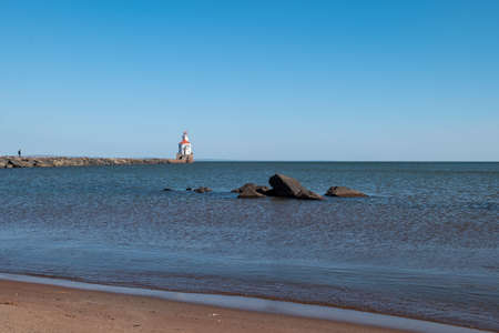 Lighthouse with red roof at the end of a pier on Lake Superior, sand beach, and large boulders surrounded by ripples of blue water.