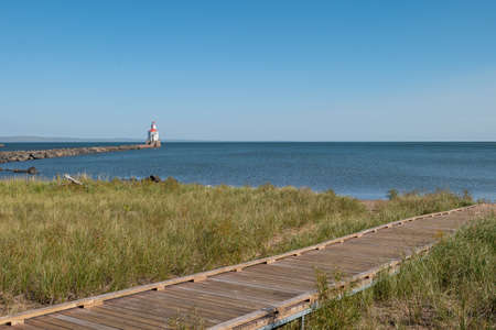 Boardwalk to Lake Superior over grass covered sand dune, a lighthouse with red roof and blue water on a sunny autumn afternoon. 스톡 콘텐츠