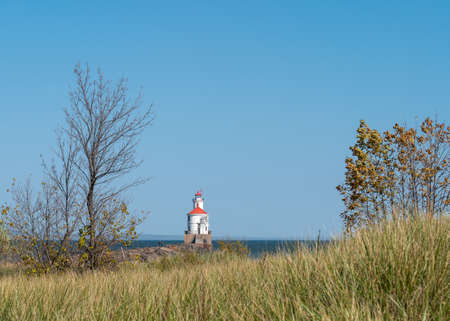 Lighthouse with red roof on Lake Superior at the end of a pier, autumn grass, trees with no leaves and blue sky on a sunny afternoon at Wisconsin Point. 스톡 콘텐츠