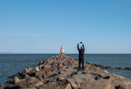 Unidentifiable photographer takes picture of a lighthouse with red roof at the end of a rocky pier on Lake Superior, with calm water and clear blue sky. 스톡 콘텐츠