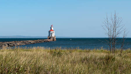 Lighthouse with red roof on Lake Superior at the end of a pier, fishing boat on the blue water, and green and tan grass on a sunny autumn afternoon.