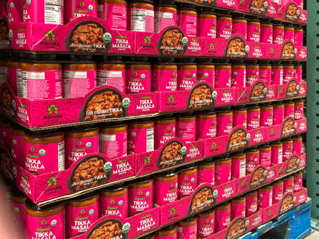 BAXTER, MN - 3 FEB 2021: Jars of organic Tikka Masala Sauce on display in a retail store shop. A pellet load of Mayura cuisine with bright pink labels. 에디토리얼
