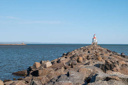 Lighthouse with red roof at the end of a rocky pier on Lake Superior, with calm water and clear blue sky. Another pier juts out into the water on the left. 스톡 콘텐츠