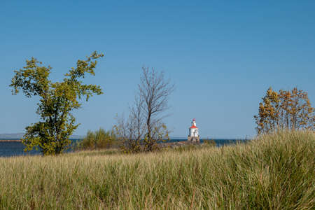 Lighthouse with red roof on Lake Superior at the end of a pier, autumn grass, trees with no leaves and blue sky on a sunny autumn afternoon at Wisconsin Point. 스톡 콘텐츠
