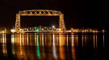 The iconic Duluth Minnesota Aerial Lift Bridge with reflections on calm harbor waters at night.