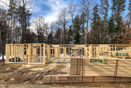 House construction site with wall studs and stacks of wood trusses on the ground, ready for installation,