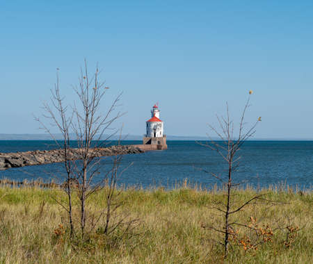 Lighthouse at end of pier, large boulders, green grass and blue lake.