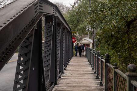 Iron truss bridge beams with many bolts.