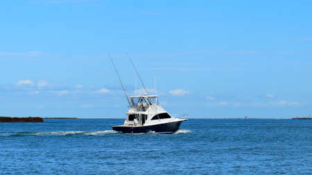 Beautiful white and black fishing yacht boat on the blue water. 스톡 콘텐츠