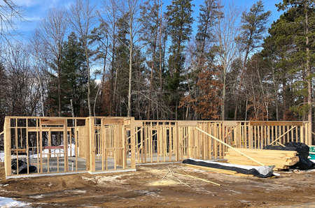 House construction site with wall studs and stacks of wood lumber. 스톡 콘텐츠