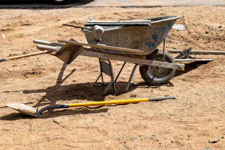 Wheel barrow and other tools used by a builder to make a concrete sidewalk.