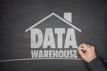 Data warehouse concept on blackboard with hand