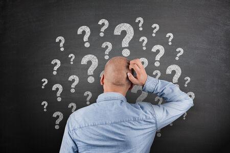 Question Mark on black Blackboard with businessman photo
