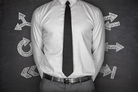 Arrows concept with businessman on black Blackboard photo