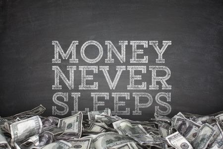 sleeps: Money never sleeps on blackboard background
