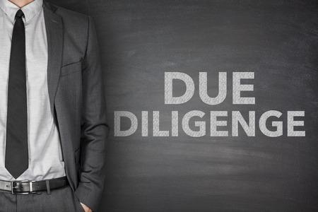 Due diligence on black blackboard with businessman