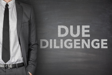 mergers: Due diligence on black blackboard with businessman
