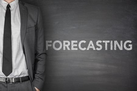 Forecasting concept on black blackboard with businessman