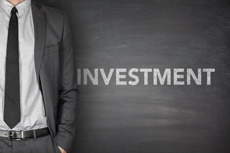 Investment word on black blackboard with businessman photo