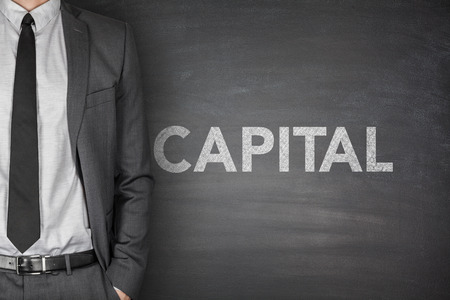 Capital word on black blackboard with businessman photo