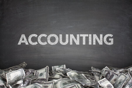 Accounting word on black blackboard with pile of dollars photo