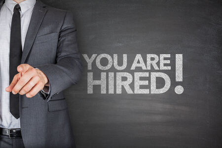 You are hired on black Blackboard with businessman photo