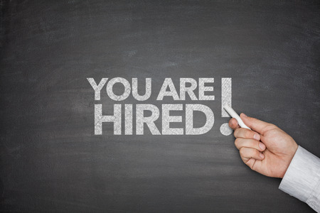 You are hired on black Blackboard with businessman hand photo