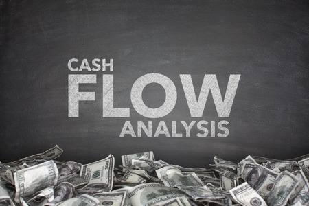 cashflow: Cash flow analysis on black blackboard with dollar bills