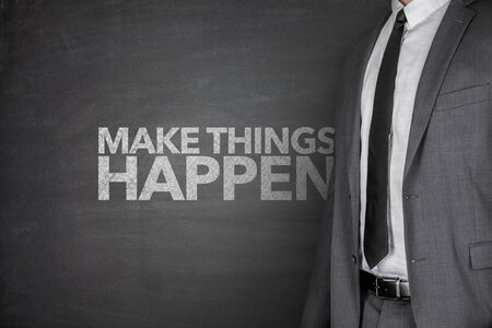 Make things happen on blackboard with businessman photo