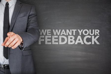 We want your feedback on blackboard with businessman hand pointing Standard-Bild
