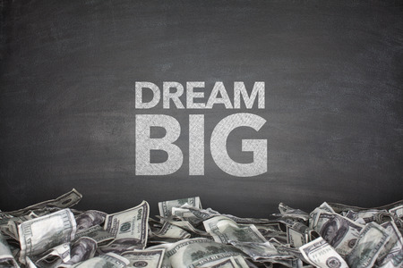 centric: Dream big on blackboard with pile of dollar bills