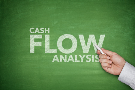 cash flow statement: Cash flow analysis on green blackboard with dollar bills