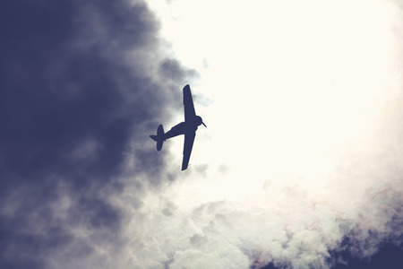 Old fighter plane on bright cloudy sky photo