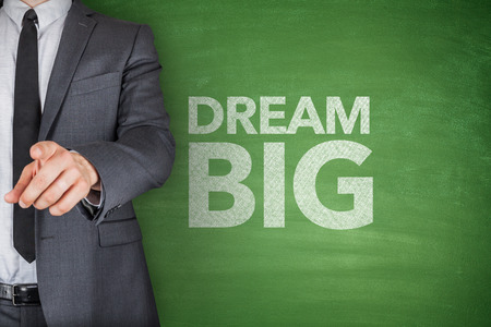 centric: Dream big on blackboard with businessman hand holding chalk