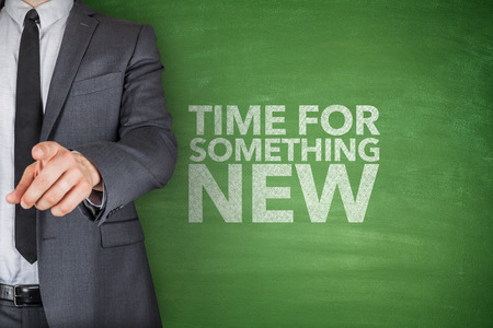 Time for something new on blackboard with businessman