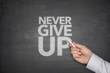 give up: Never give up on blackboard with hand