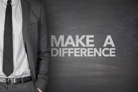 to make: Make a difference on black blackboard with businessman Stock Photo